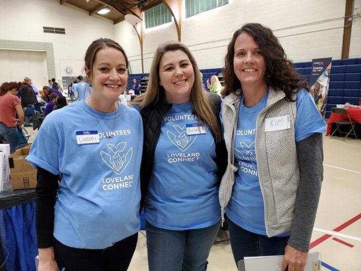3 Female Volunteers for Loveland Connect Inside A School Gym