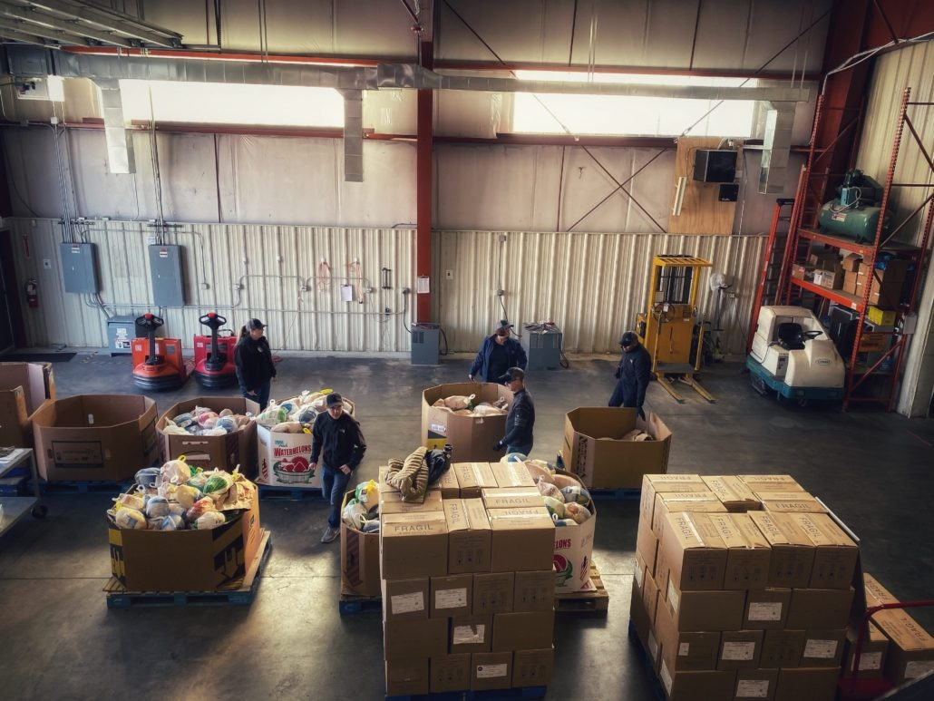 Produce & Groceries Inside of A Warehouse With Warehouse Workers